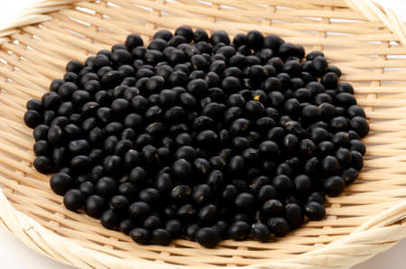 uncooked black beans on bamboo sieve on white background