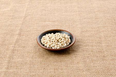 Job's tears( Adlay millet)  in a black plate on burlap background