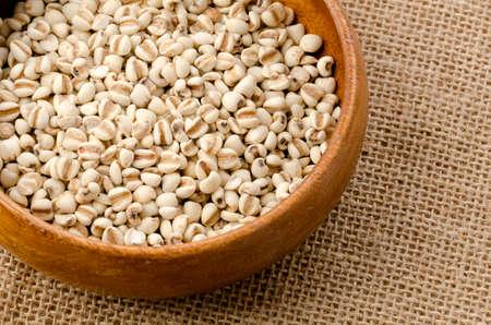 Job's tears( Adlay millet) in wooden bowl on burlap background