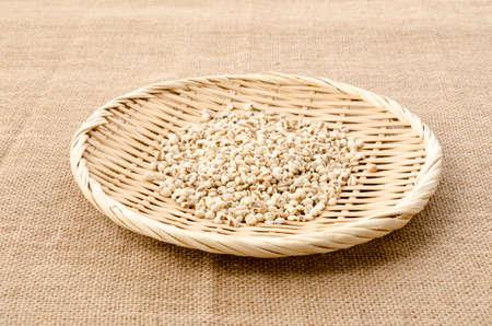 Job's tears( Adlay millet) on bamboo sieve on burlap background