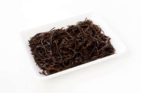 Hijiki seaweed in foam tray on white background 免版税图像