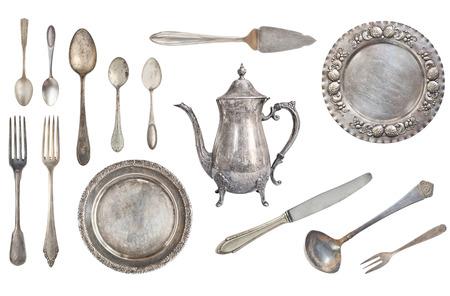 Forchette, cucchiai, coltelli, bollitore, piatti, mestolo e paletta per la torta in argento vintage. Vecchi piatti e posate isolati su sfondo bianco. Rustico. retrò. Archivio Fotografico