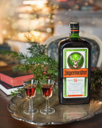 Happy new year or christmas background with Jagermeister alcohol drink, elixir. Bottle of Jagermeister with glasses on a vintage tray on the background of books. Christmas still life. Winter. Celebration. Alcohol that is drunk in the winter when it is cold.