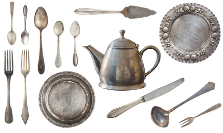 Vintage silver forks, spoons, knives, kettle, plates, ladle and scoop for the cake. Old dishes and cutlery isolated on white background. Rustic. Retro.