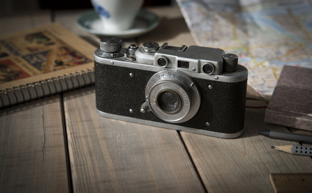 Vintage analogue film camera on a wooden table, map, notepad, pencil. Copy space