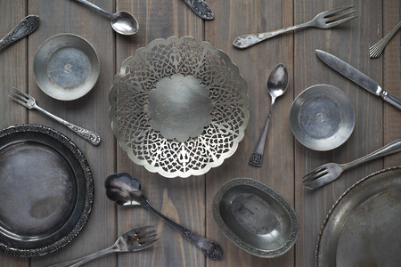 vintage spoons, forks, knives and metal plates on a gray wooden background Stock Photo