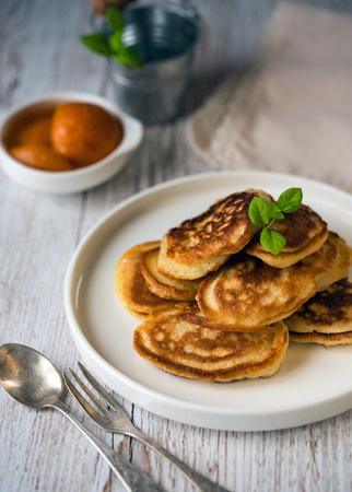 Shrove Tuesday, pancake day.  Pancakes poured with honey on the background of vintage plates, forks and knives. Shrovetide.