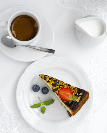 Coffee, milk and cake with strawberry on white plates on a white table. View from above. Flat lay. Imagens