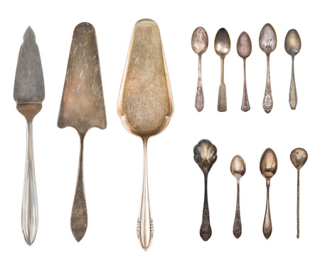 Vintage Silverware, antique spoons, forks, knives, ladle, cake shovels, kettle, tray and ice bucket isolated on isolated white background. Antique silverware. Retro.