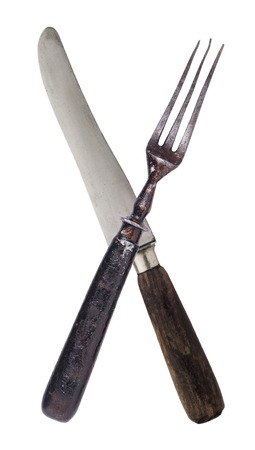 Beautiful old vintage crossed knife and fork isolated on white background. Top view. Retro silverware.