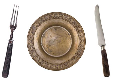 Vista dall'alto di un piatto, una forchetta e un coltello. Posate d'epoca. Isolato su sfondo bianco