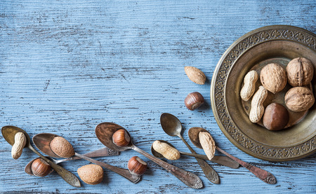 Nuts on a beautiful background and vintage spoons. Background to advertise nuts. Walnuts, peanuts, hazelnuts on a vintage plate.