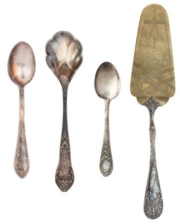 Argenteria antica dell'annata isolata su fondo bianco. Cucchiaini retrò, forchette, coltelli, pale per torta.