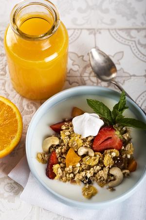Breakfast. Muesli with milk or yogurt, nuts and strawberries, orange juice and orange