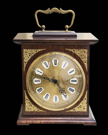 Vintage beautiful clock with a wooden case and gold jewelry isolated on black Stockfoto