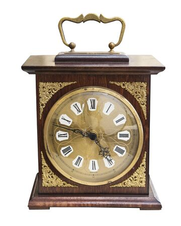 Vintage beautiful clock with a wooden case and gold jewelry isolated on white background