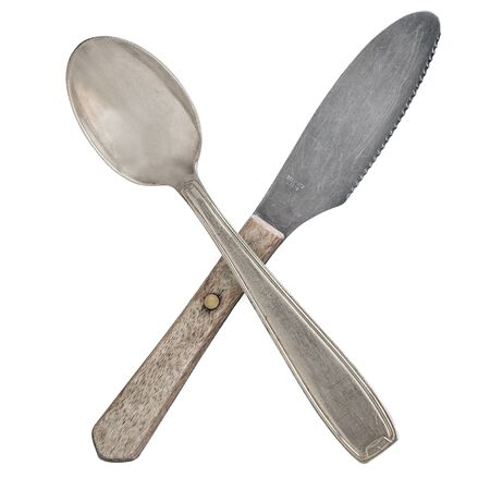 Crossed vintage crossed spoon and knife isolated on bell background. Rustic style Stockfoto