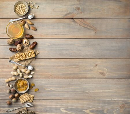 Nuts, dried fruits, honey and old spoons and forks on a wooden table background. Copy spase.
