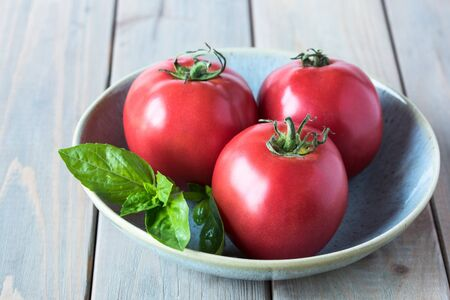 Ripe raspberry-pink  tomatoes on a beautiful plate on a wooden table. Copy space. Stockfoto