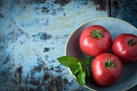 Ripe three tomatoes and basil on a beautiful plate on a on a concrete table. Copy space.