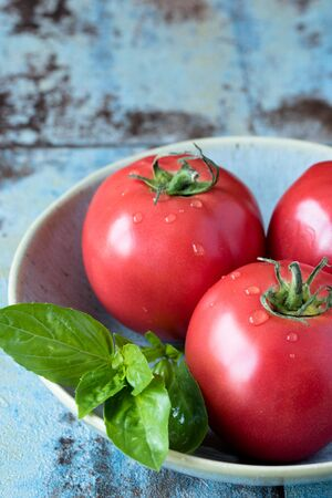 Ripe three tomatoes and basil on a beautiful plate on a wooden table. Copy space. Stockfoto