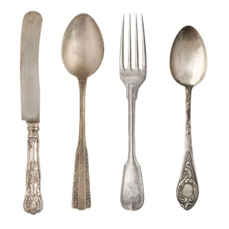 Vintage worn out knifes and forks isolated on a white background. Retro silverware. Imagens