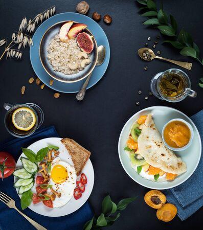 Flat lay. Menu. Three breakfasts, oatmeal, fried eggs, pancakes, tea, tea background. Copy space.