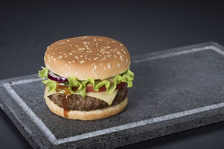 Hamburger with a double serving of meat, tomatoes, salad, onions on a wooden board in a restaurant.Copy space