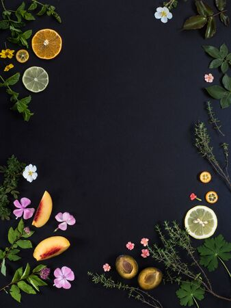 Background for the menu. Black stone background with fruits, flowers and green leaves. Copy space.  Stockfoto