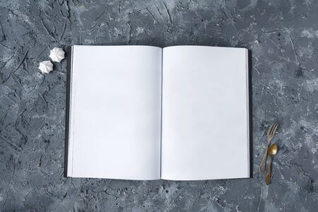 Opened book, white pages, on a gray concrete background, vintage spoons and forks, meringues, for restaurant menu, white pages, on a gray concrete background, vintage spoons and forks, meringues, for restaurant menu