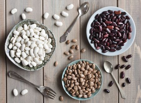 Beans, three types of beans in plates on a background of a white wooden table, vintage spoons and fork