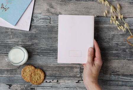 Hand holds a sheet of paper on a wooden table background, milk, cookies, notebooks. Copy space