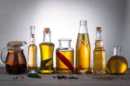 Oil in bottles with butter, olive oil with herbs and spices on the table