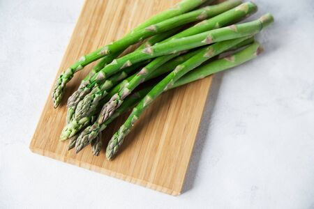 Green fresh asparagus on a wooden board on a white background. Copy space.  Banco de Imagens