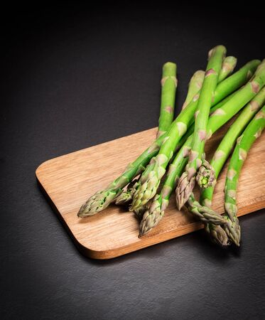 Green fresh asparagus on a wooden board on a black background. Copy space.  Stock Photo