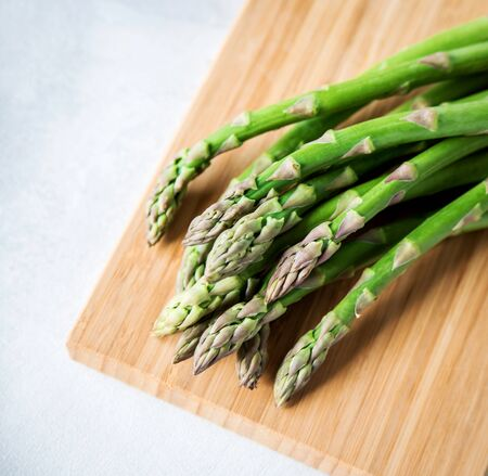 Green fresh asparagus on a wooden board on a white background. Copy space.  Stockfoto