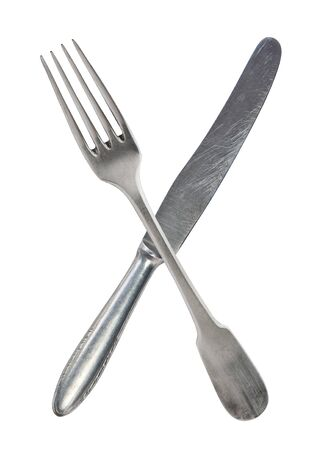 Crossed vintage crossed fork and knife isolated on bell background. Rustic style