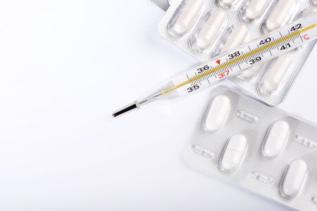 Pills and thermometer on a white background, the concept of a flu epidemic.