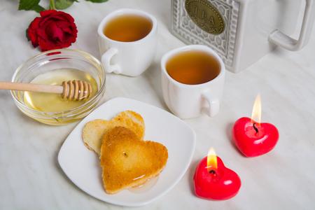 bougie coeur: Petit-déjeuner facile pour la Saint-Valentin - deux morceaux de pain, miel, thé et roses en arrière-plan Banque d'images