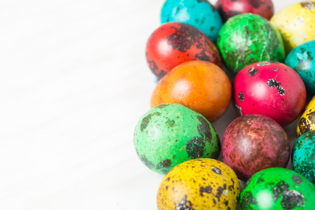 Color quail eggs on the white background with copy space