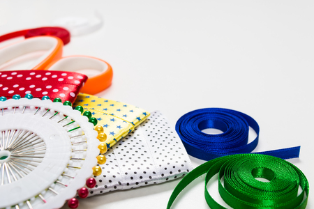 taping: Scissors, pins and color tapes for sewing on white background