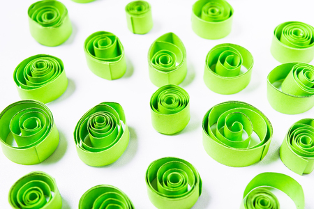 Quilling art. Green paper curls on the white background Stock Photo