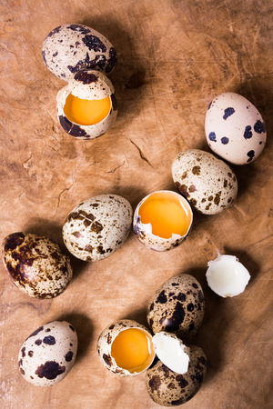 huevos de codorniz: Raw quail eggs on the wooden background with some open eggs