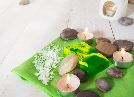 Spa still life with salt, stone and green soap with aroma lamp on the white wooden table Stock Photo
