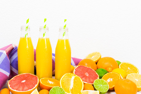 red straw: Citrus lemonade in the bottles with fruit ingredients (orange, lemon, lime, grapefruit, kumquat) and tissue on the white background with copy space Stock Photo