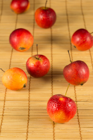 Fresh mini red apples on the straw background