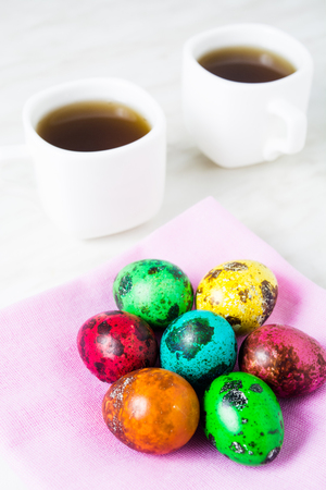 Easter breakfast with color quail eggs two cup of tea on the white background Stock Photo