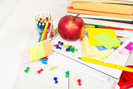 School stationary and apple on the white wooden table. Back to school concept