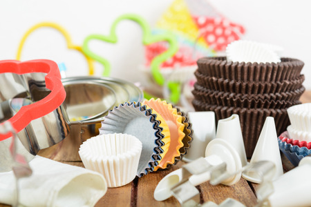 cutter: Different baking accessories over brown wooden table and white background