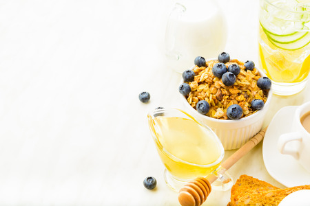 Muesli with honey, milk and blueberry like breakfast with detox water, coffee, bread with copy space on white background